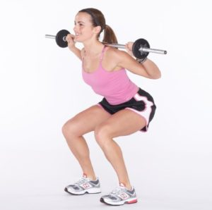 Woman doing squat exercise with barbell